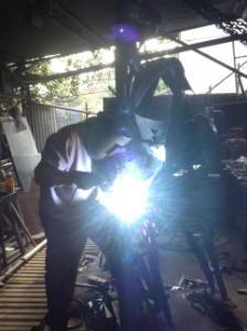 Steve Cornish volunteer welds the Lewis gun to the sculpture